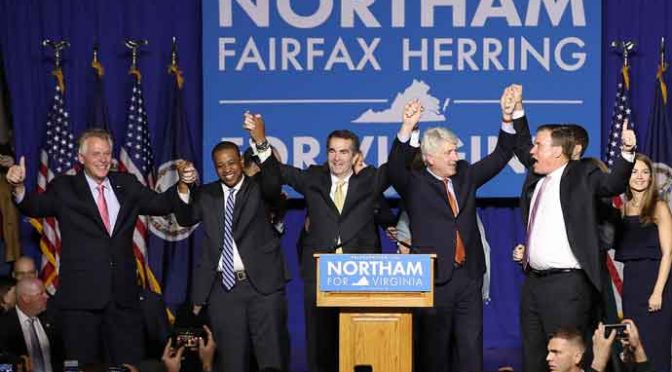 FAIRFAX, VA - NOVEMBER 07: Gov.-elect Ralph Northam (C) links arms with (L-R) current Gov. Terry McAuliffe, Lt. Gov.-elect Justin Fairfax, Attorney General-elect Mark Herring, and U.S. Sen. Mark Warner (D-VA) at an election night rally November 7, 2017 in Fairfax, Virginia. Northam defeated Republican candidate Ed Gillespie. (Photo by Win McNamee/Getty Images)