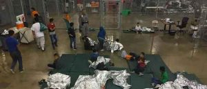 Migrants form a line outside of one of the cages. (Image: YouTube)