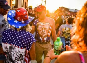 STURGIS, SD - AUGUST 07: Johne Riley walks down Main Street showing off his chest painted with a portrait of President Donald Trump during the 80th Annual Sturgis Motorcycle Rally on August 7, 2020 in Sturgis, South Dakota. While the rally usually attracts around 500,000 people, officials estimate that more than 250,000 people may still show up to this year's festival despite the coronavirus pandemic.