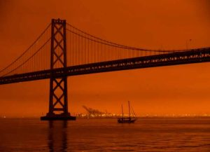 SAN FRANCISCO, CA - SEPTEMBER 09: A ship passes beneath the Bay Bridge as smoke from various wildfires burning across Northern California mixes with the marine layer, blanketing San Francisco in darkness and an orange glow on September 9, 2020 in San Francisco, California. Over 2 million acres have burned this year as wildfires continue to burn across the state.