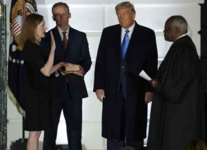 WASHINGTON, DC - OCTOBER 26: U.S. President Donald Trump (2R) watches as U.S. Supreme Court Associate Justice Amy Coney Barrett (L) is sworn in by Supreme Court Associate Justice Clarence Thomas (R) as her husband Jesse Barrett (2L) holds a bible during a ceremonial swearing-in event on the South Lawn of the White House October 26, 2020 in Washington, DC. The Senate confirmed Barrett's nomination to the Supreme Court today by a vote of 52-48.