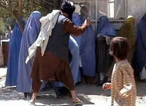 Taliban religious police beating a woman in Kabul on 26 August 2001