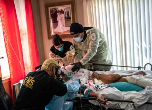 YONKERS, NY - APRIL 06: Medics wearing personal protective equipment (PPE), intubate a gravely ill patient with COVID-19 symptoms at his home on April 06, 2020 in Yonkers, New York. The man, 92, was barely breathing when they arrived, and they performed a rapid sequence intubation (RSI), on him before transporting him by ambulance to St. John's Riverside Hospital. The medics (L-R) are Capt. AJ Briones (paramedic), Michelle Melo (EMT), Carlos Cabrera (EMT). The Empress EMS employees treat and transport patients to hospitals throughout Westchester County and parts of New York City, the epicenter of the coronavirus pandemic in the United States. (Image: Getty)