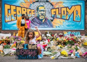 MINNEAPOLIS, MN - JUNE 9: A girl holds her fist in the air while visiting the memorial for George Floyd on June 9, 2020 in Minneapolis, Minnesota. Residents of the community, and people around the world, have come together in calling for an end to police brutality after the death of George Floyd, who was killed while in Minneapolis police custody on May 25th.