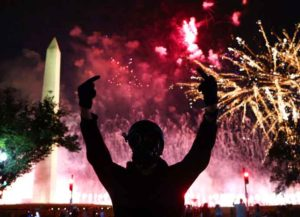 WASHINGTON, DC - AUGUST 27: (EDITORS NOTE: Image contains obscene gesture) A protester gestures as fireworks explode above the Washington Monument during a protest on the fourth night of the Republican National Convention on August 27, 2020 in Washington, DC. Protesters gathered as U.S. President Donald Trump accepts the Republican nomination for a second term.