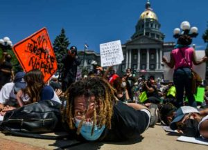 """DENVER, CO - MAY 30: Jevon Sutton yells, """"I can't breathe,"""" while joining thousands of people as they stage a die-in next to the Colorado State Capitol with their hands behind their backs to protest the death of George Floyd on May 30, 2020 in Denver, Colorado. The city of Denver has enacted a curfew starting Saturday night and Governor Jared Polis has called in the Colorado National Guard after two nights of protests wreaked havoc across the city."""