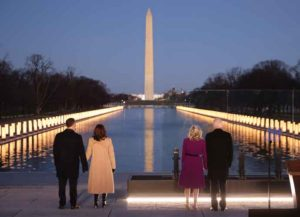 WASHINGTON, DC - JANUARY 19: (L-R) Douglas Emhoff, U.S. Vice President-elect Kamala Harris, Dr. Jill Biden and U.S. President-elect Joe Biden look down the National Mall as lamps are lit to honor the nearly 400,000 American victims of the coronavirus pandemic at the Lincoln Memorial Reflecting Pool January 19, 2021 in Washington, DC. As the nation's capital has become a fortress city of roadblocks, barricades and 20,000 National Guard troops due to heightened security around Biden's inauguration, 200,000 small flags were installed on the National Mall to honor the nearly 400,000 Americans killed by COVID-19. (Photo by Chip Somodevilla/Getty Images)