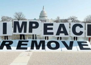 WASHINGTON, DC - JANUARY 12: People gather at the base of the U.S. Capitol with large IMPEACH and REMOVE letters on January 12, 2021 in Washington, DC. The group is calling on Congress to impeach and remove President Donald Trump on the day that Democrats introduced articles of impeachment in response to Trump's incitement of a mob entering the U.S. Capitol Building on January 6. (Photo by Paul Morigi/Getty Images for MoveOn)