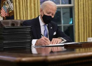 WASHINGTON, DC - JANUARY 20: U.S. President Joe Biden prepares to sign a series of executive orders at the Resolute Desk in the Oval Office just hours after his inauguration on January 20, 2021 in Washington, DC. Biden became the 46th president of the United States earlier today during the ceremony at the U.S. Capitol. (Photo by Chip Somodevilla/Getty Images)