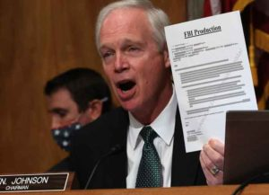 WASHINGTON, DC - DECEMBER 03: Senate Homeland Security Committee Chairman Ron Johnson (R-WI) holds up a redacted document during a hearing about the Crossfire Hurricane investigation in the Dirksen Senate Office Building on Capitol Hill on December 03, 2020 in Washington, DC. Crossfire Hurricane is the code name for the FBI's 2016 counterintelligence investigation into possible links between President Donald Trump's associates and Russian officials. A Justice Department Inspector General report found no political bias in the initiation of the investigation, which resulted in the Mueller Report finding that the Trump campaign did not conspire or coordinate with the Russian government. (Photo by Chip Somodevilla/Getty Images)