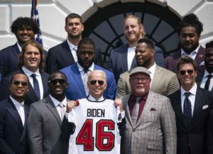 U.S. President Joe Biden, center, holds up a football jersey during a ceremony for the Tampa Bay Buccaneers on the South Lawn of the White House in Washington, D.C., U.S., on Tuesday, July 20, 2021. The Buccaneers defeated the Kansas City Chiefs 31-9 at Super Bowl LV in Tampa, Florida, on February 7. Photographer: Al Drago/Bloomberg via Getty Images
