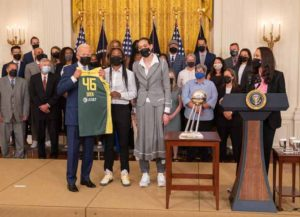 U.S. President Joe Biden holds up a jersey while hosting the Seattle Storm in the East Room of the White House in Washington, D.C., U.S., on Monday, Aug. 23, 2021. Biden is honoring the team after they beat the Indiana Fever during the 2020 WNBA Championship. Photographer: Ken Cedeno/UPI/Bloomberg via Getty Images